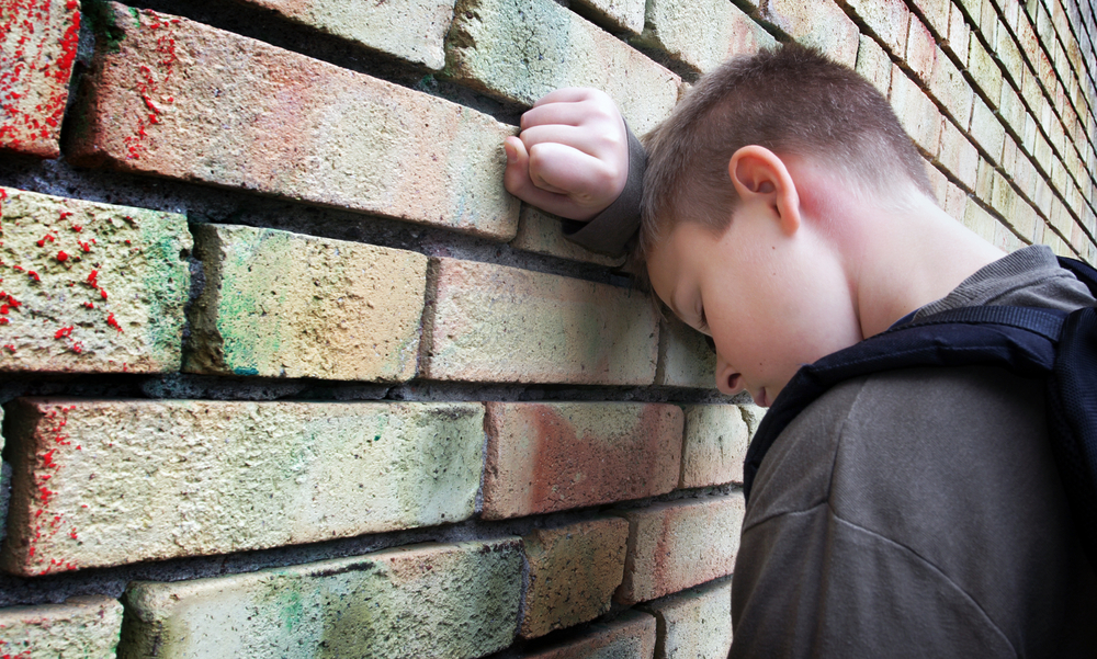 despondent child head against wall